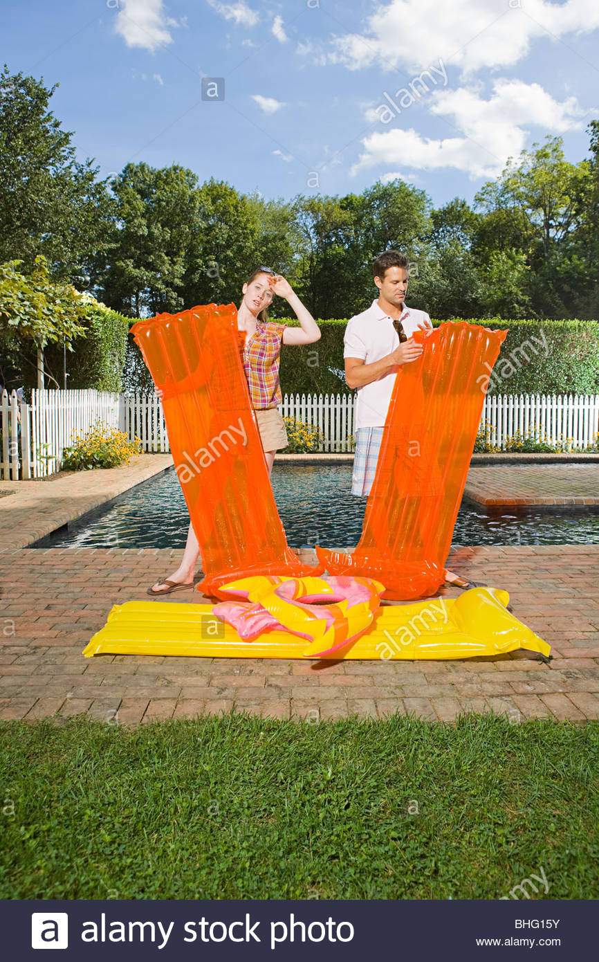 Couple inflating air mattresses - Stock Image