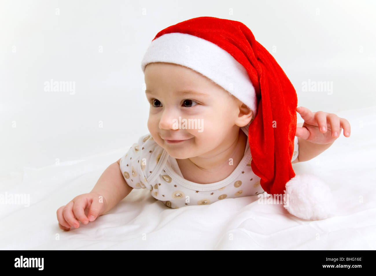 portrait of adorable baby boy in Santa hat on white background - Stock Image