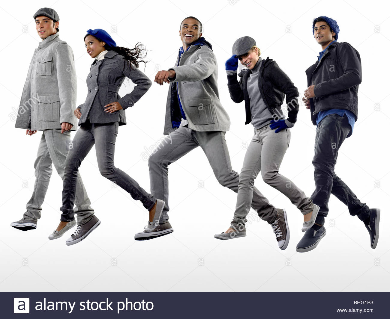 Five young people in coats jumping - Stock Image