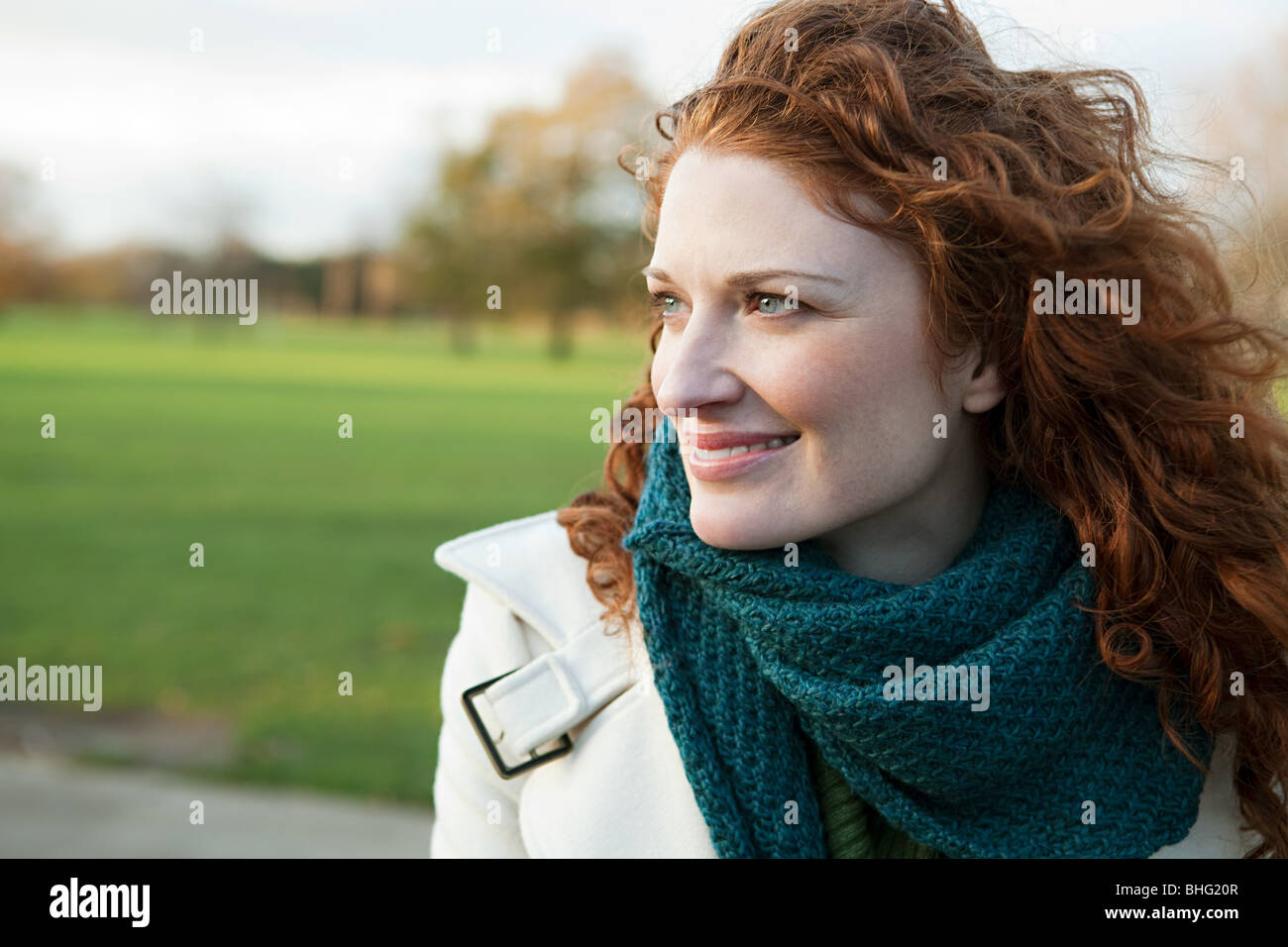 Portrait of a smiling red haired woman - Stock Image