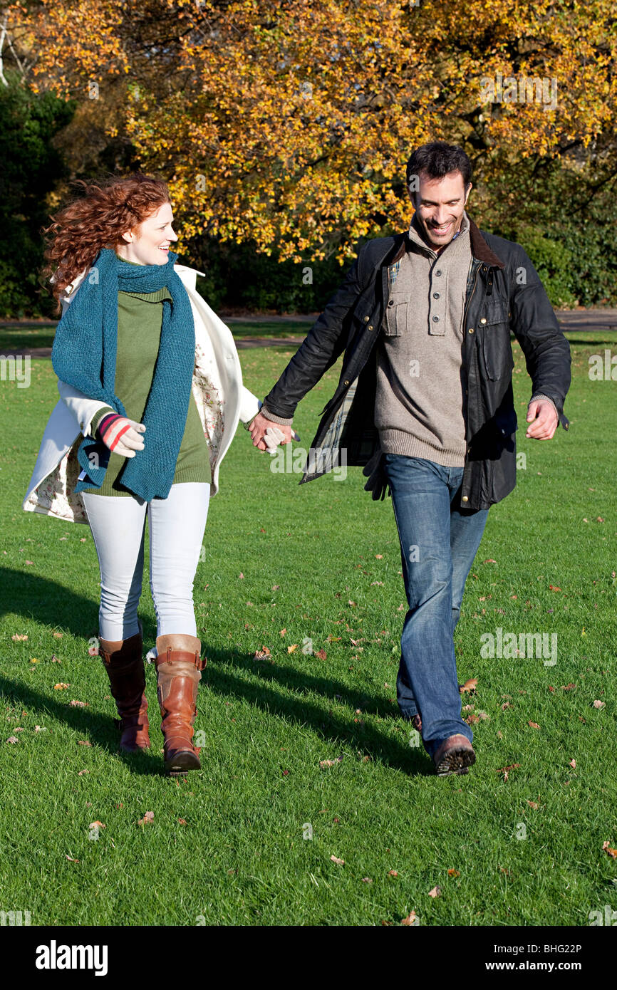 A mid adult couple hold hands in dulwich park - Stock Image