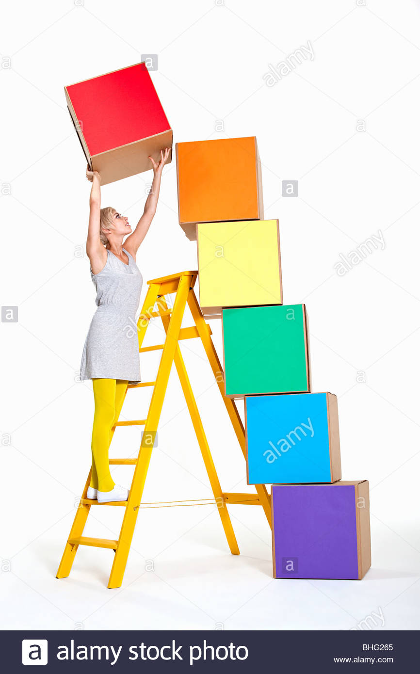 Woman stacking coloured boxes - Stock Image