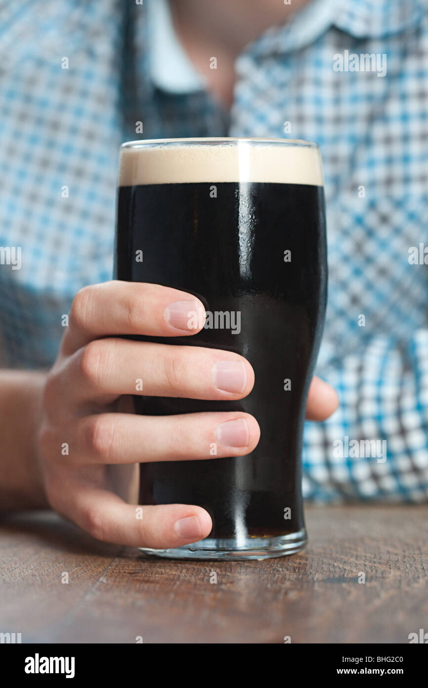Young man holding pint glass, close up - Stock Image