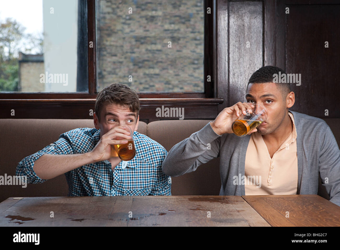 Young men drinking beer in bar Stock Photo
