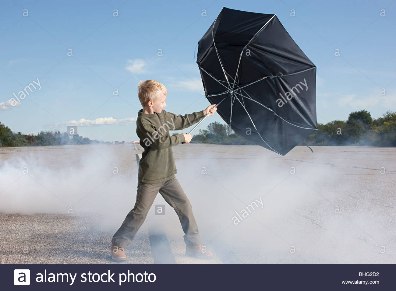 Boy on runway with umbrella - Stock Image