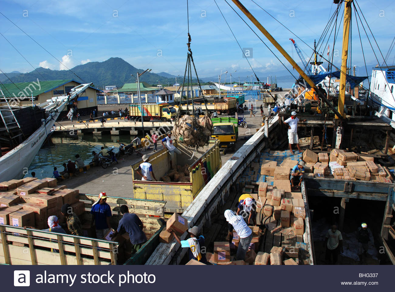 Man helps direct a cargo net of cement sacks being lowered into yellow truck on jetty Bima harbor Sumbawa Timur - Stock Image