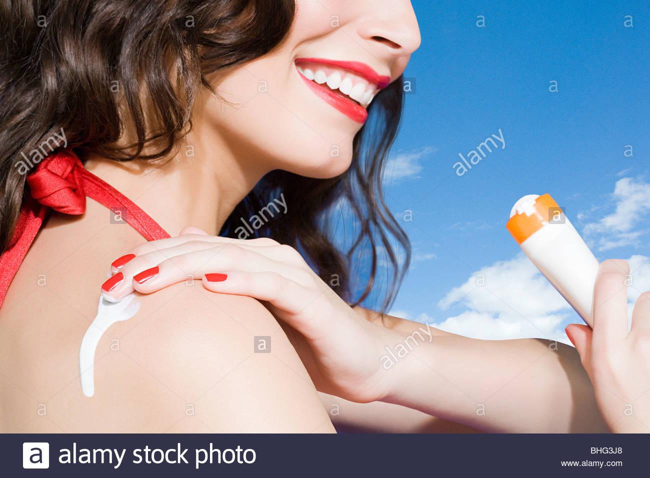 Young woman applying suncream - Stock Image