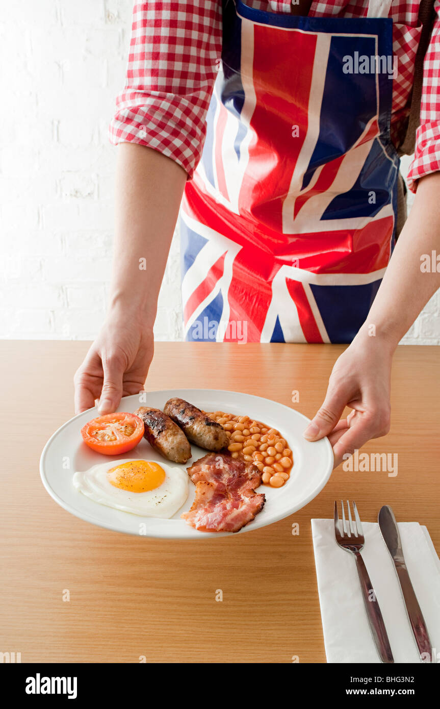 Person serving english breakfast - Stock Image