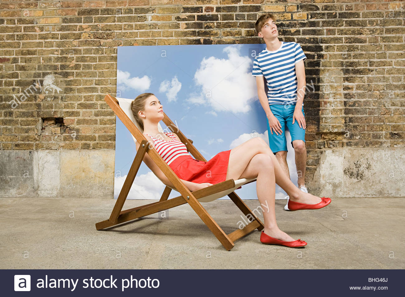 Teen couple with deckchair and sky backdrop - Stock Image