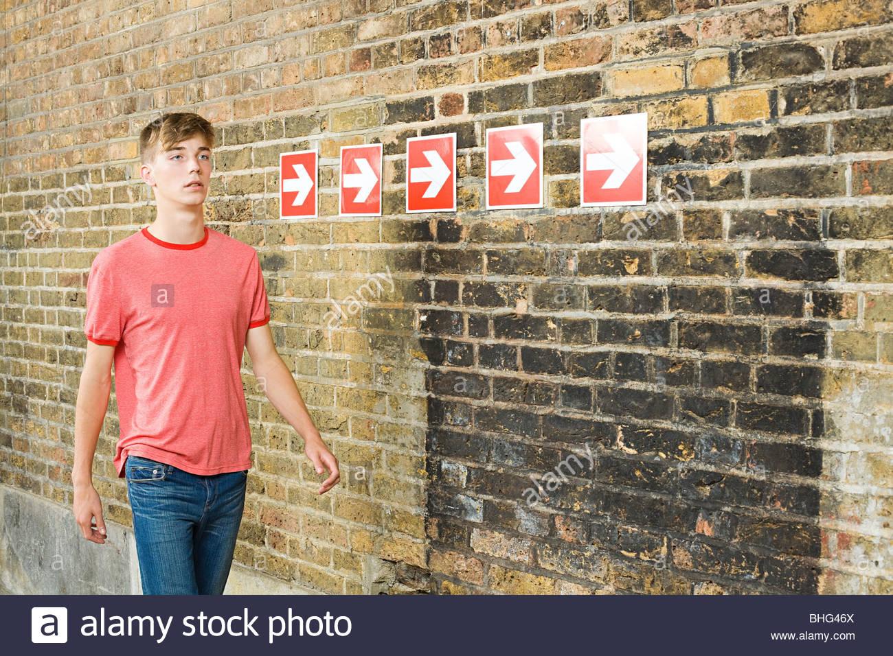 Teenage boy and row of arrows - Stock Image