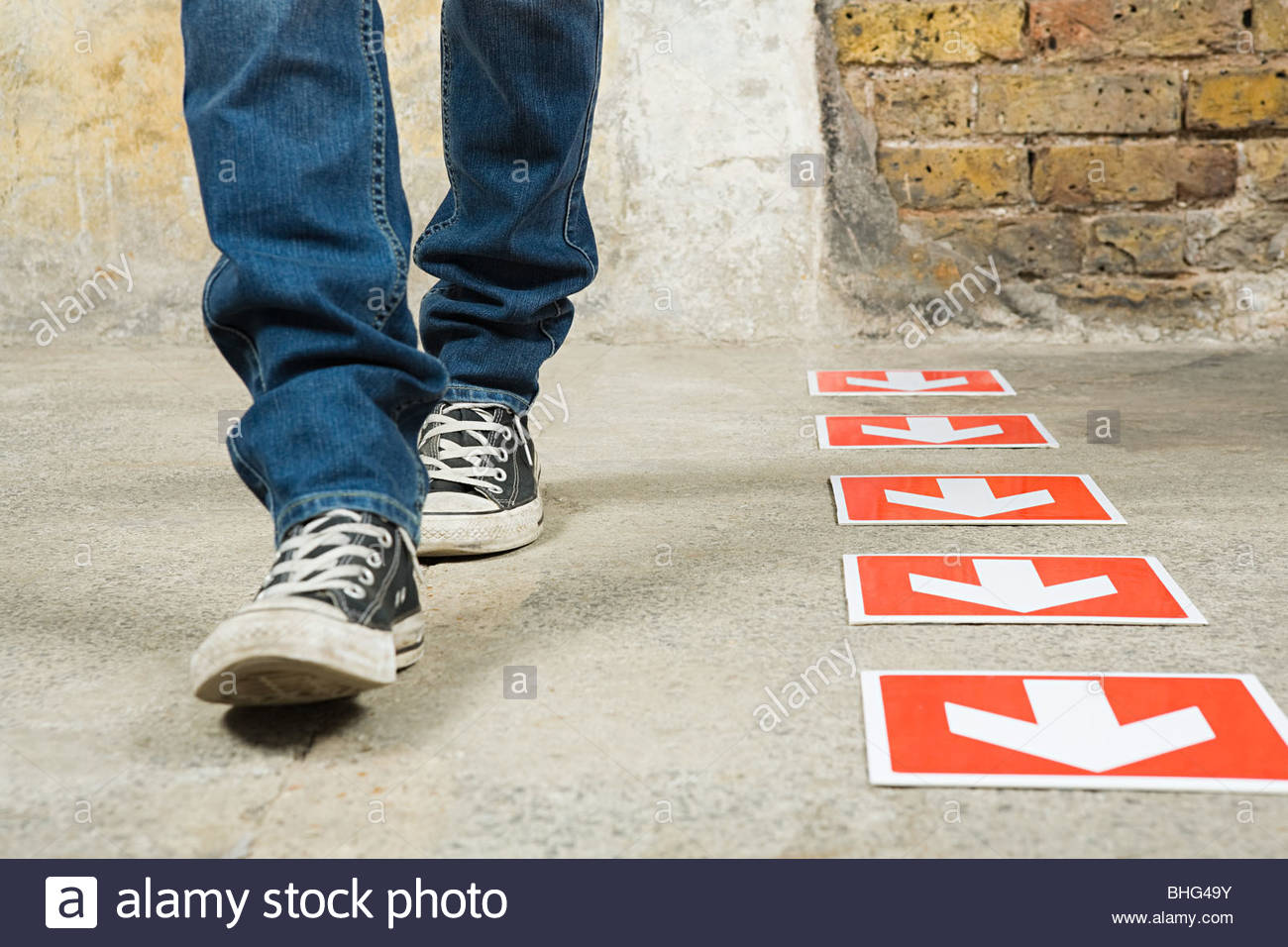 Person walking by arrows - Stock Image