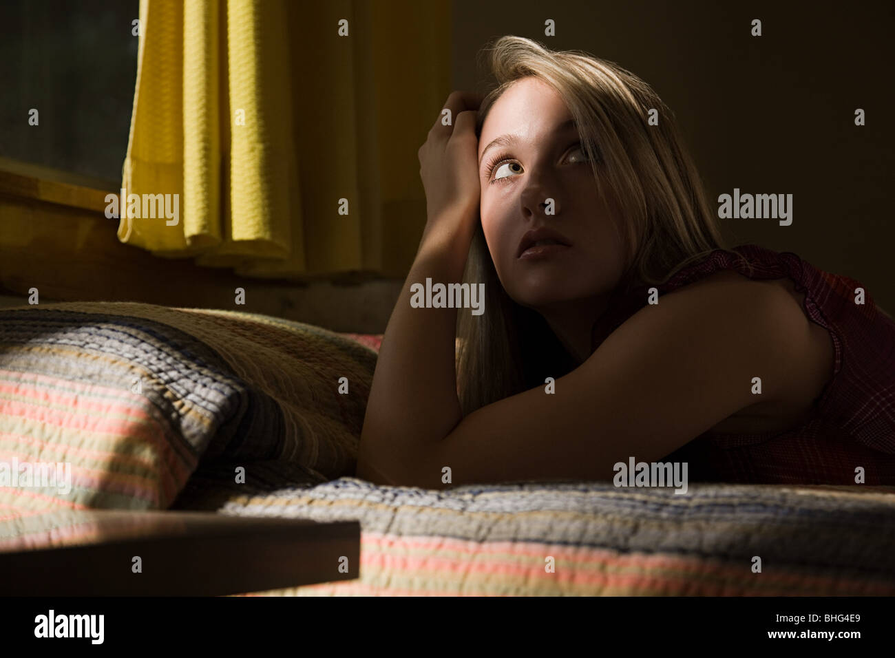 Young woman on bed in shadows - Stock Image