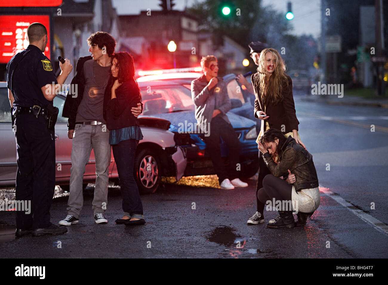 Young people and police officer at scene of car crash - Stock Image