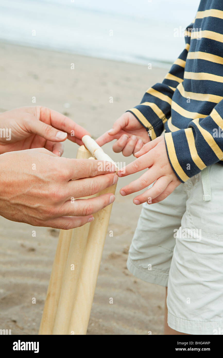 Adult and child setting up crickets stumps - Stock Image