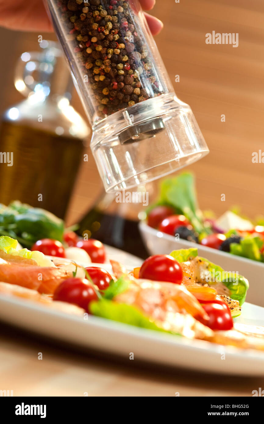 A pepper mill grinding pepper onto a seafood salad of smoked salmon and shrimp or prawns - Stock Image