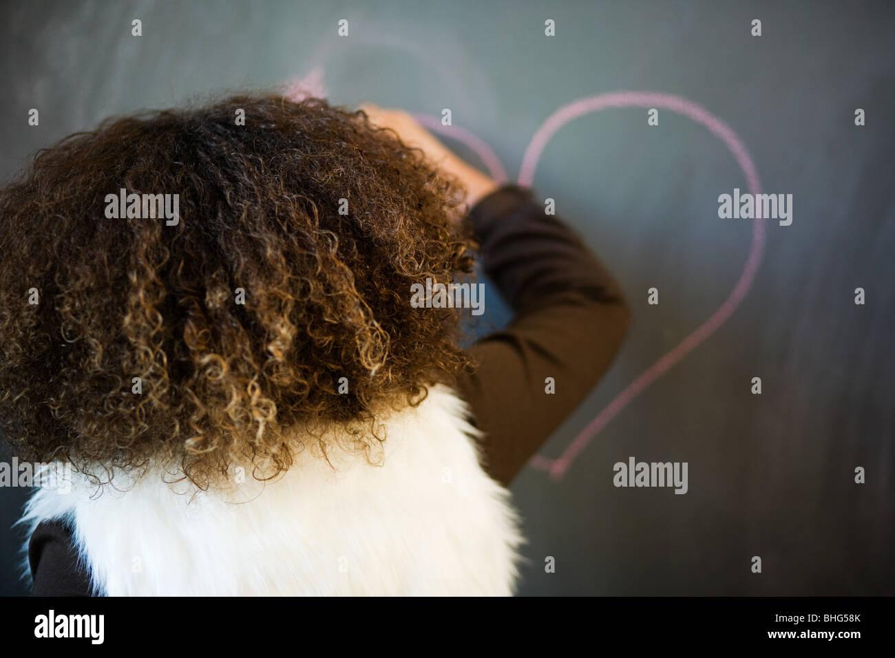 Girl drawing heart on blackboard - Stock Image