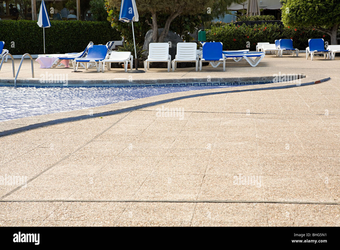 Sun loungers beside a swimming pool - Stock Image