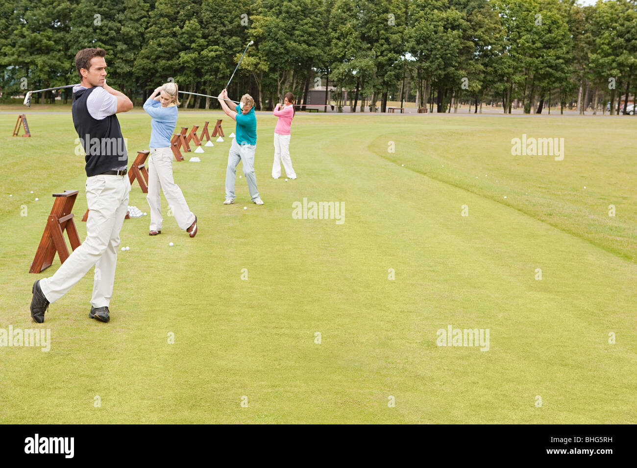 Four golfers on the driving range - Stock Image