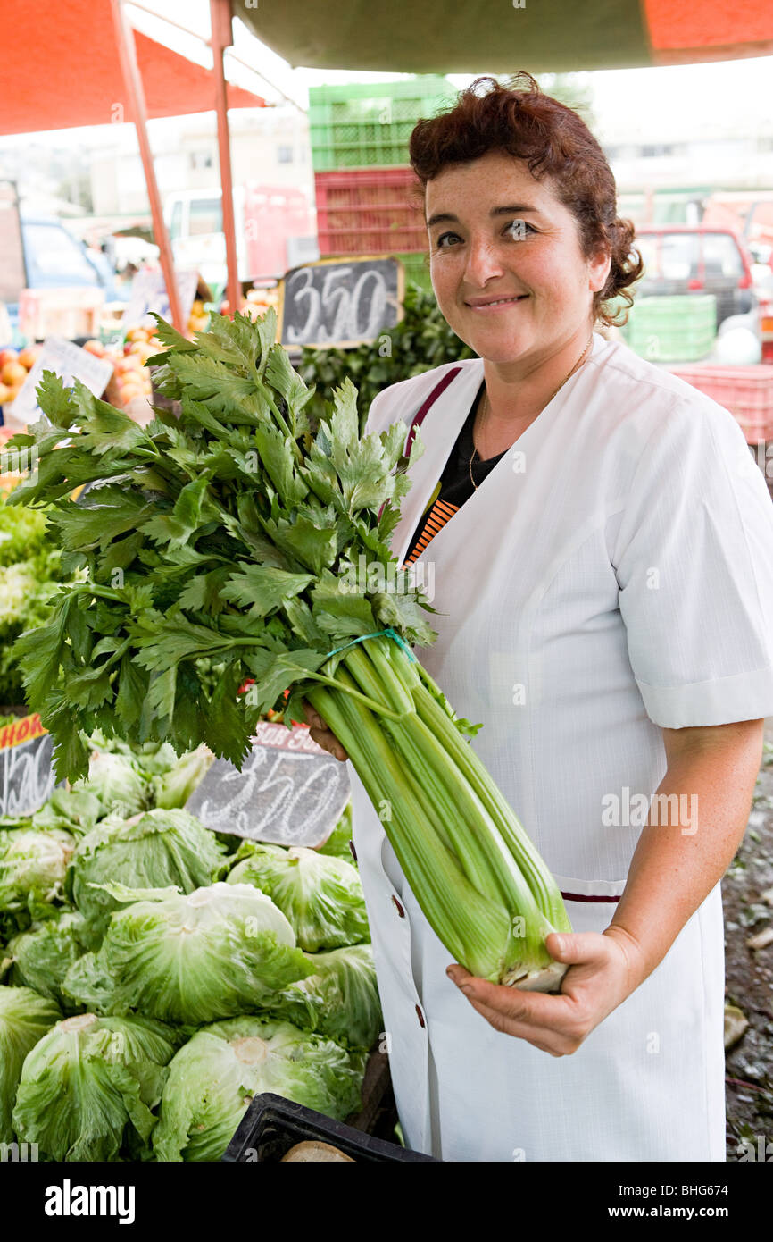 Market trader with celery - Stock Image