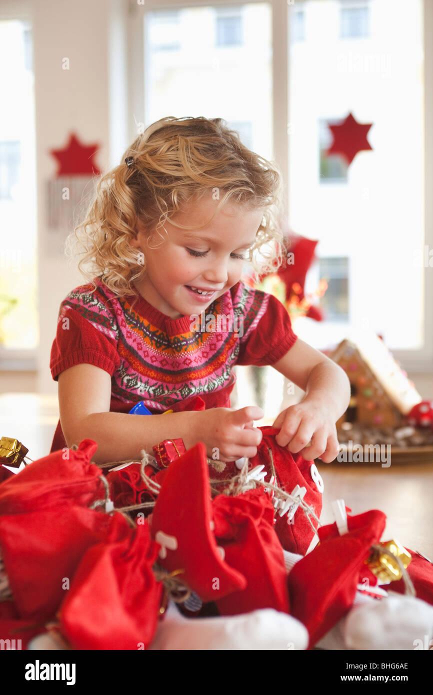 young girl playing with gift sacks - Stock Image