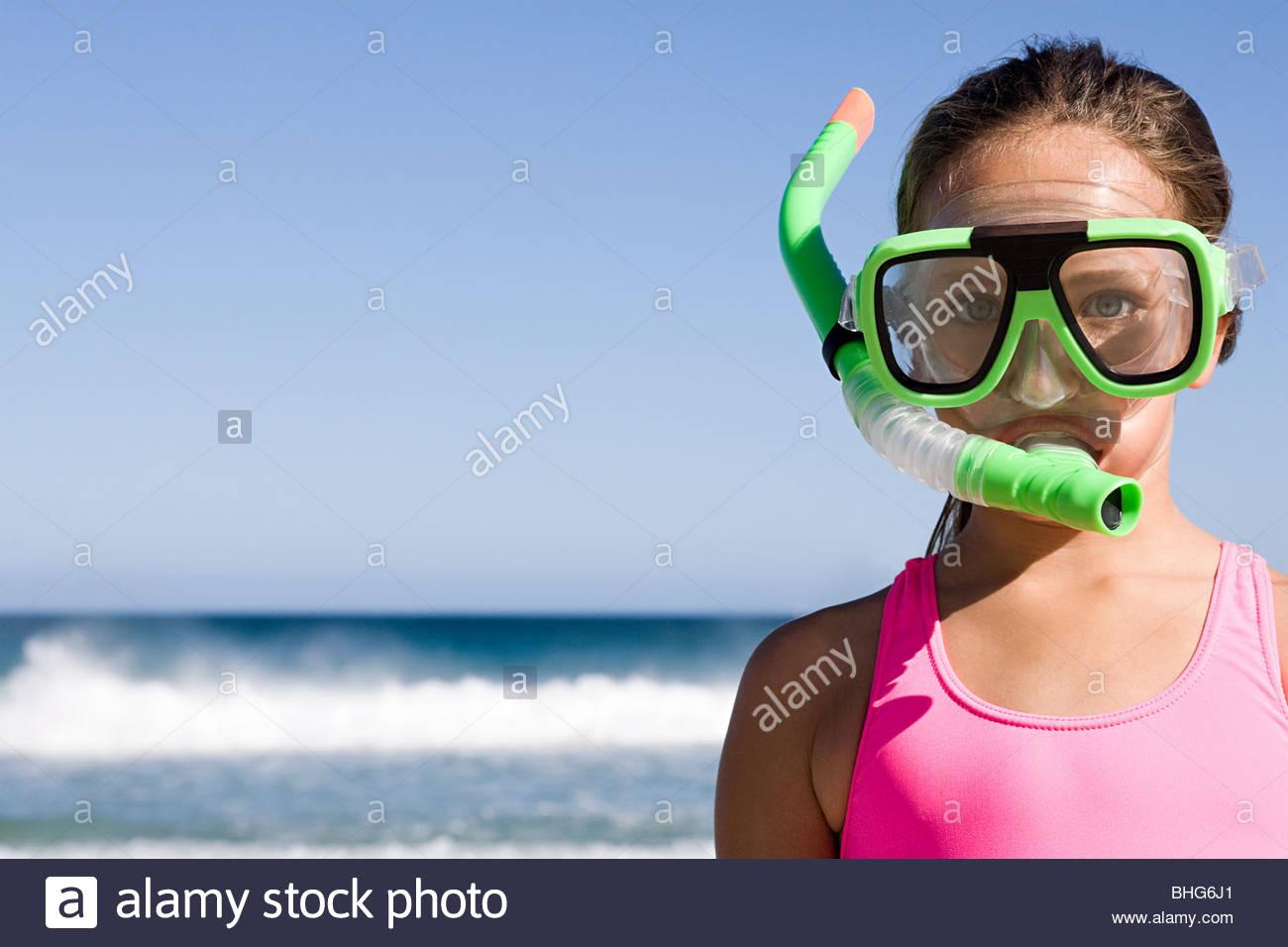 Little girl standing in front of ocean wearing snorkel mask - Stock Image
