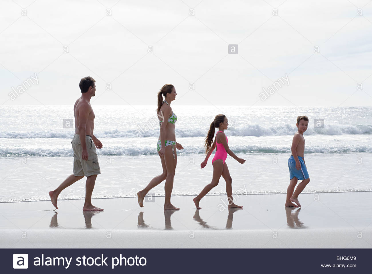Family walking along the beach by the water's edge - Stock Image
