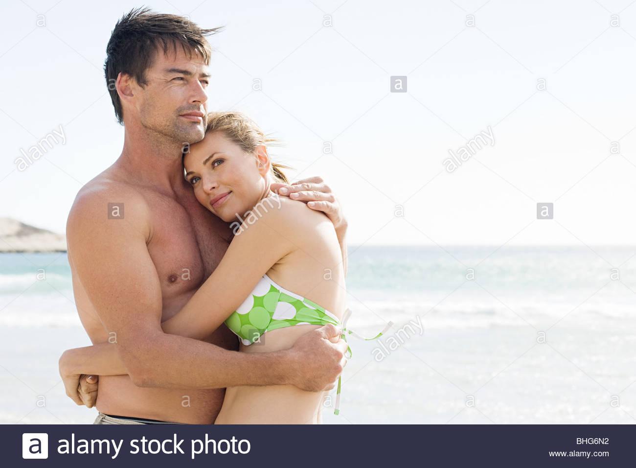 Couple in swimwear embracing on the beach - Stock Image