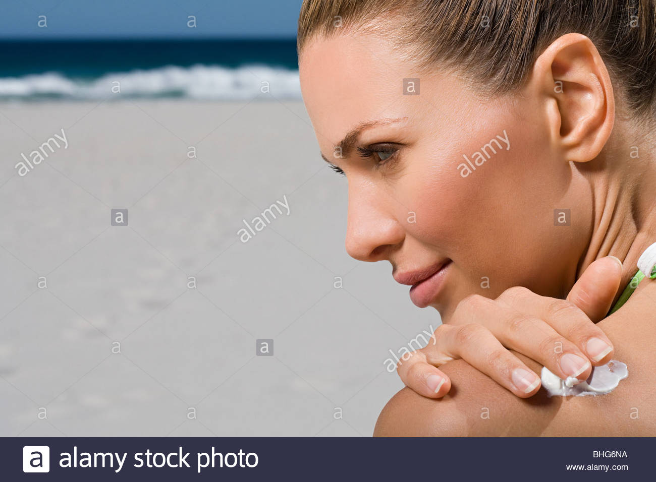 Woman sitting on beach rubbing sunblock onto shoulder - Stock Image