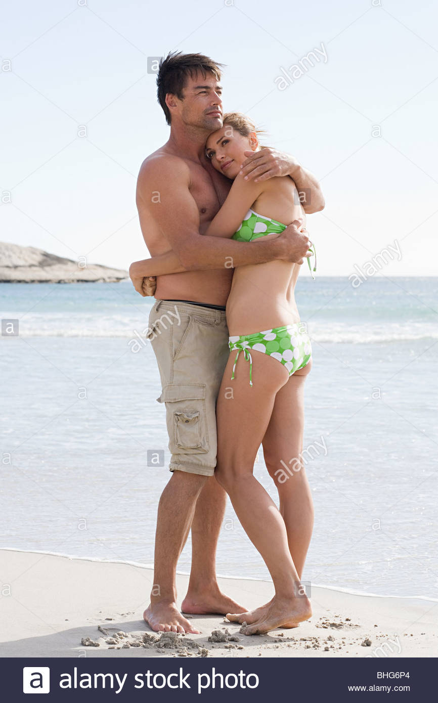 Couple embracing by water's edge at the beach - Stock Image