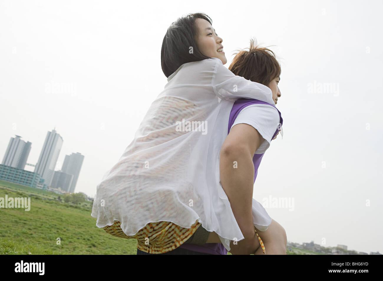 Young man giving girlfriend piggyback - Stock Image