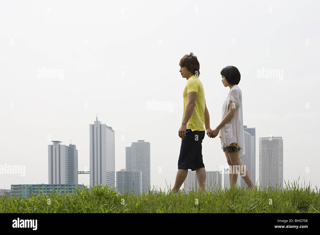 Young couple walking by city skyline - Stock Image