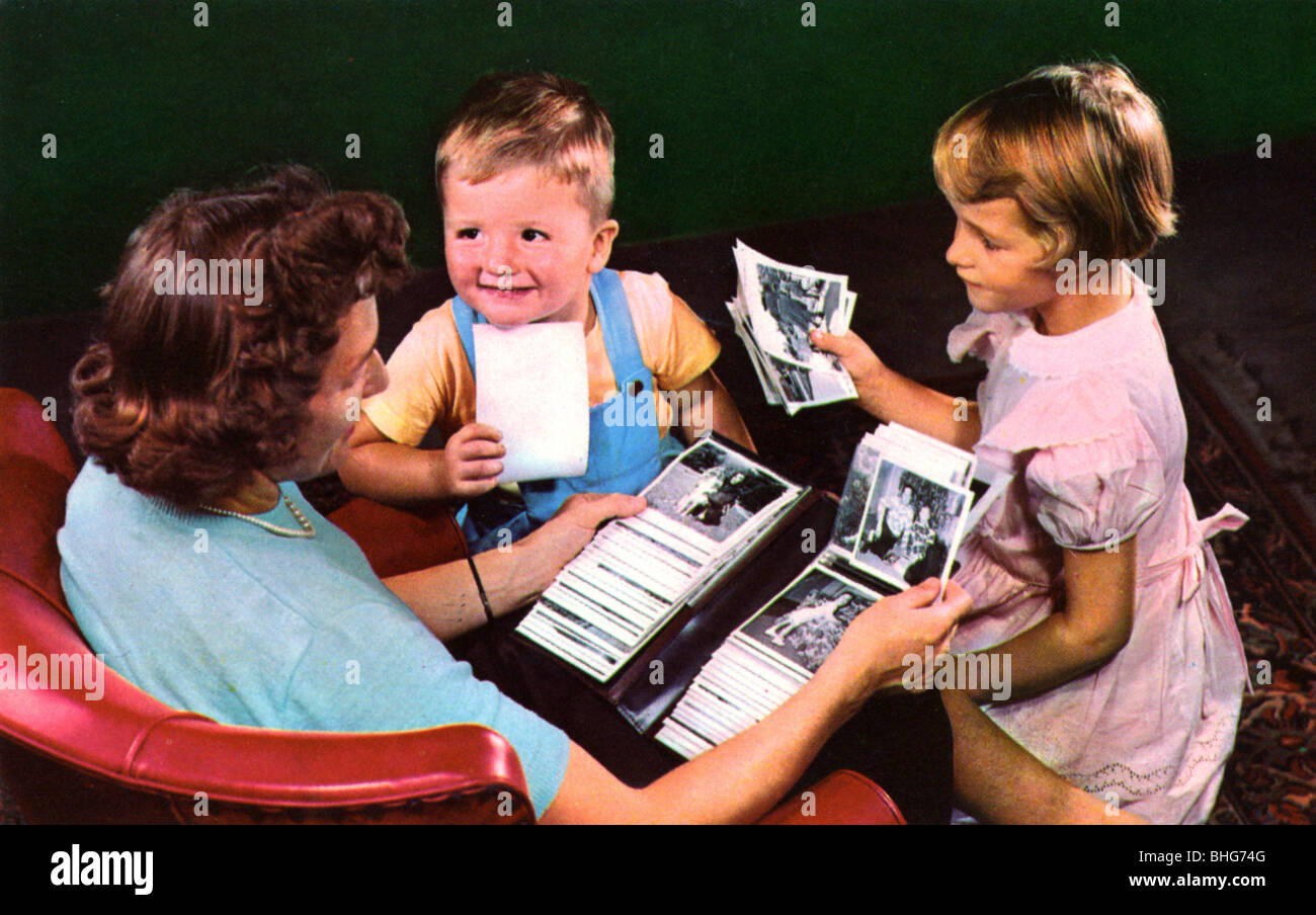 A mother and children looking at photos in a family album, Blackwood, New Jersey, USA, 1956. Artist: Unknown Stock Photo