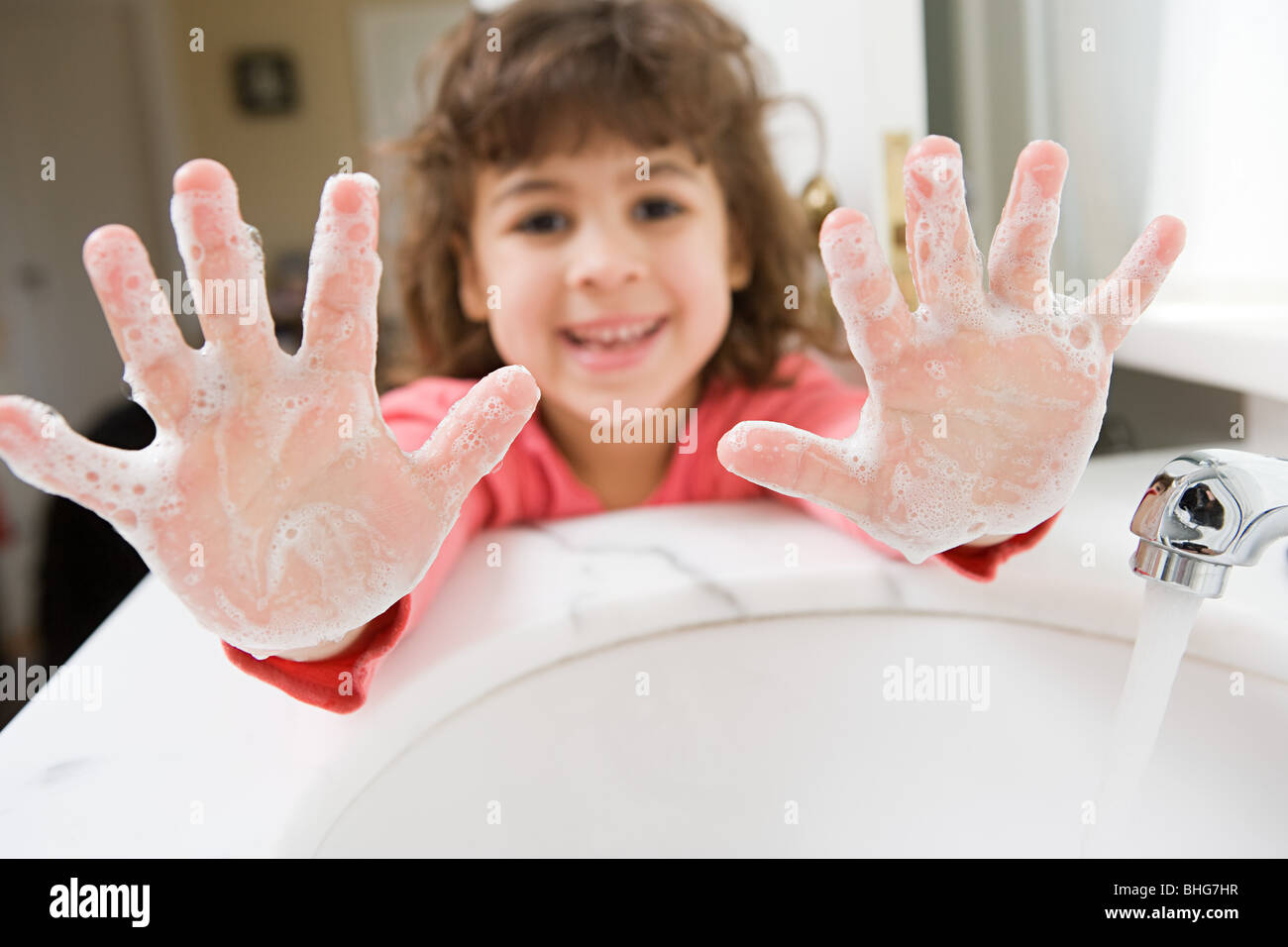 Girl with soap on her hands - Stock Image