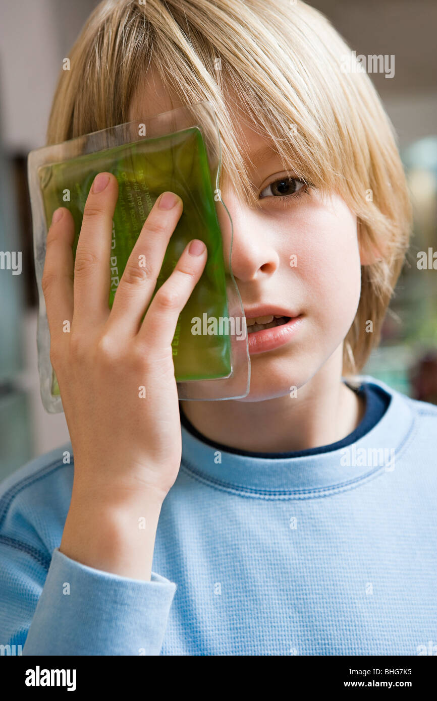 Boy with ice pack on his eye - Stock Image