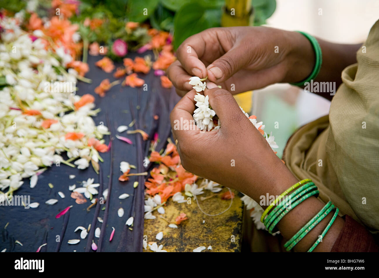 Woman making wreaths from jasmine flowers - Stock Image