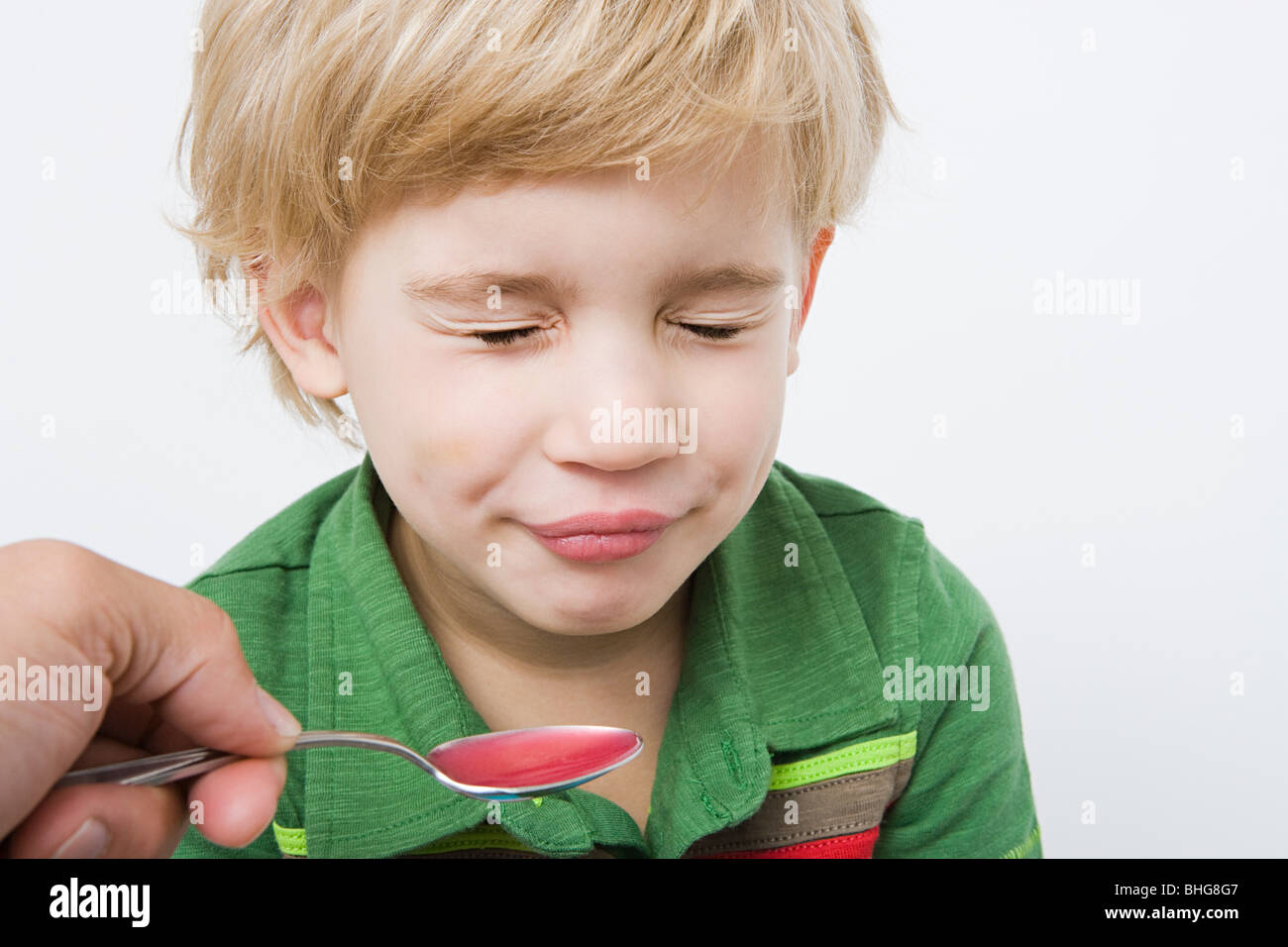 Boy and spoon of medicine - Stock Image