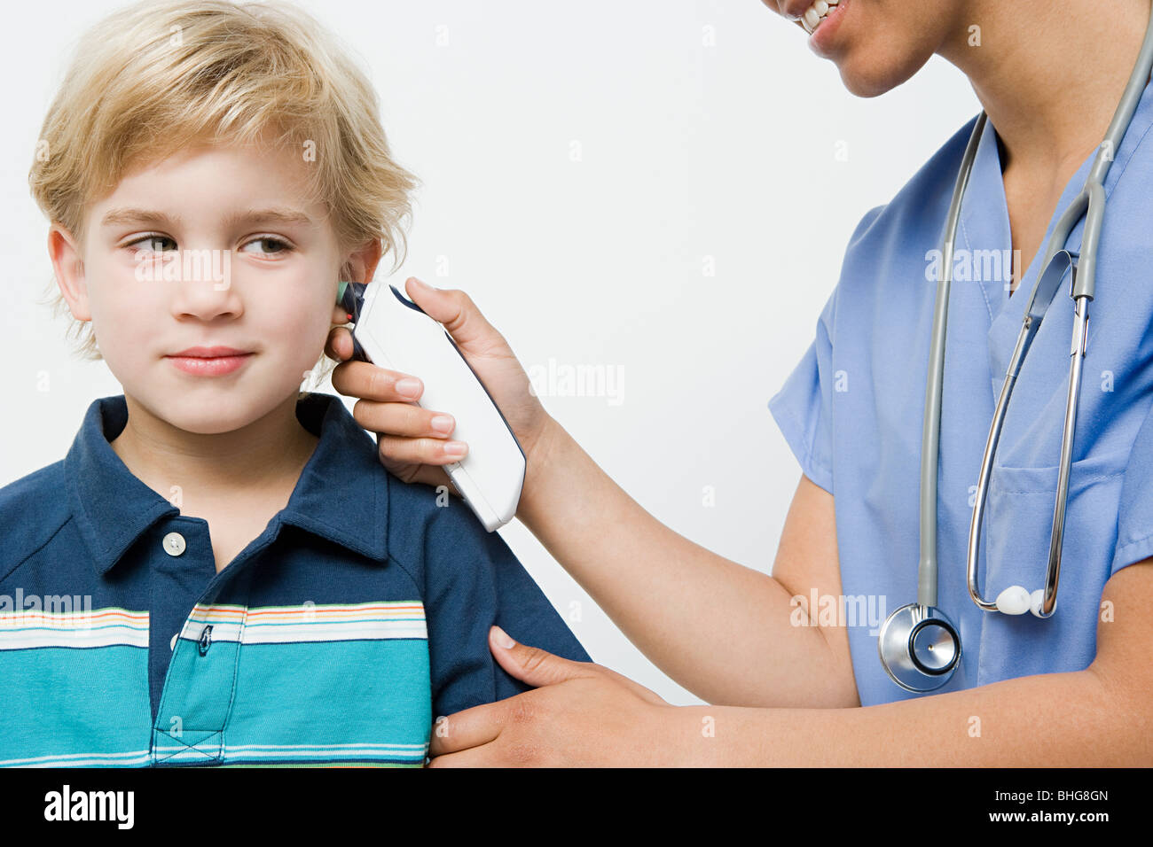 Boy with thermometer in ear - Stock Image