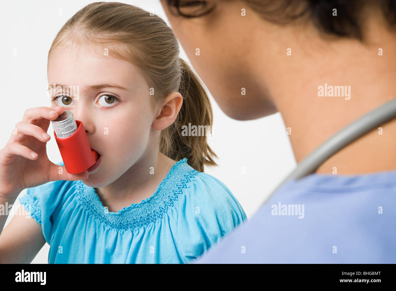 Girl taking asthma inhaler - Stock Image