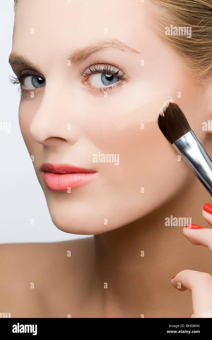 Woman applying foundation - Stock Image