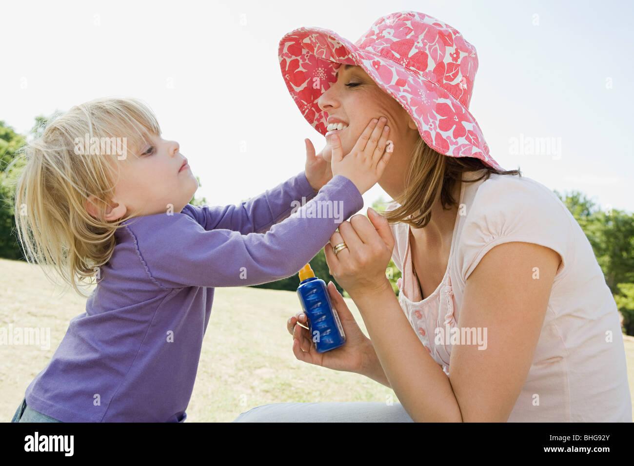 Girl putting suncream on mother - Stock Image