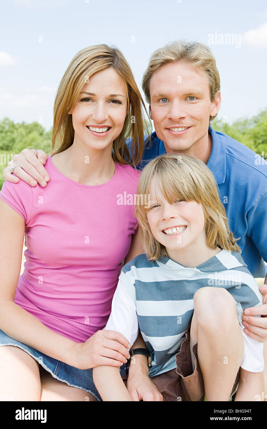 Boy outdoors with parents Stock Photo