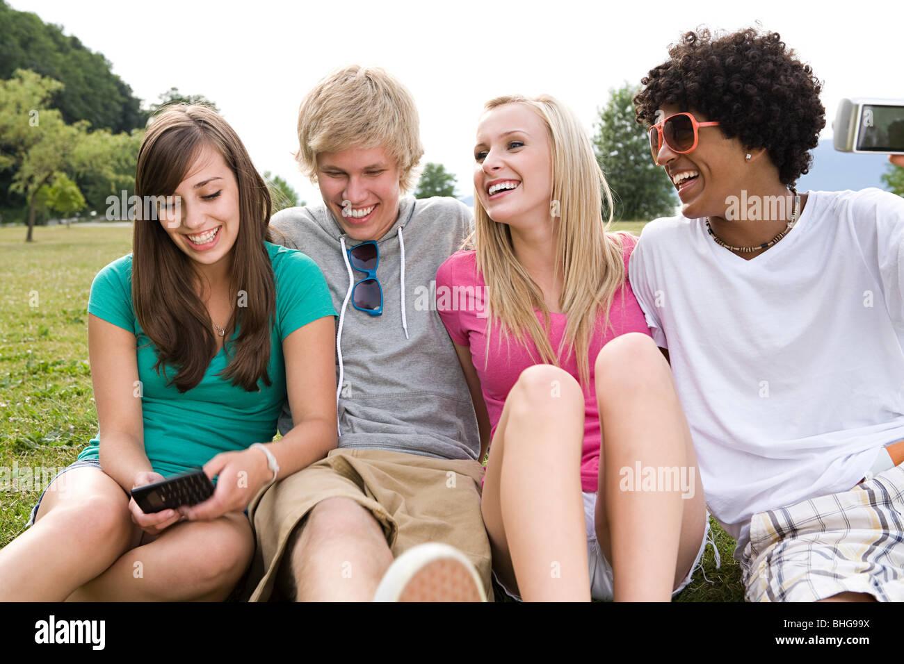 Teenage friends in park - Stock Image