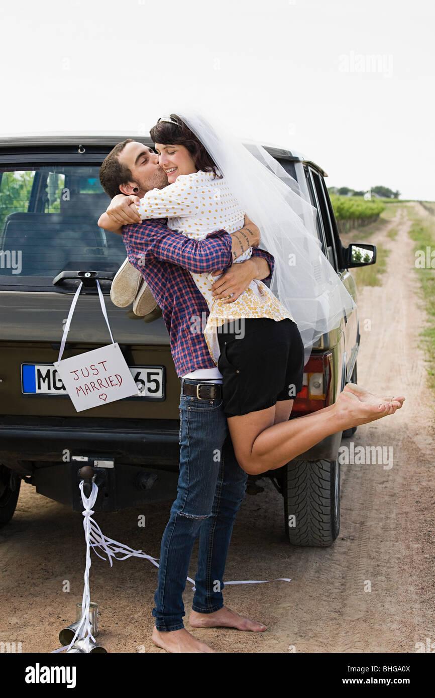Newlywed couple by vehicle - Stock Image