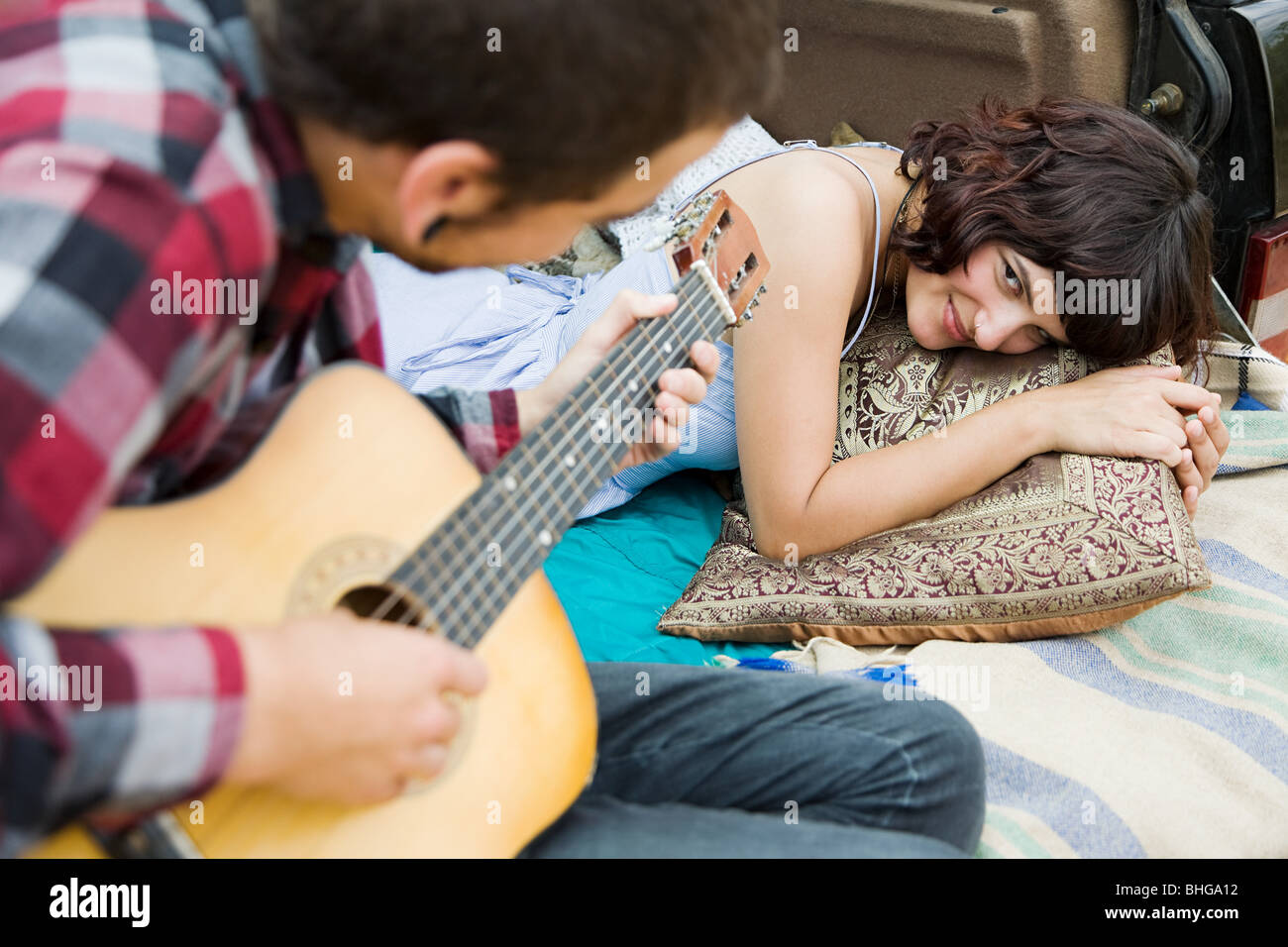 Young man playing guitar to girlfriend - Stock Image
