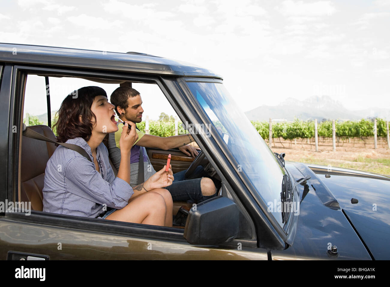 Woman putting on lipstick in vehicle - Stock Image