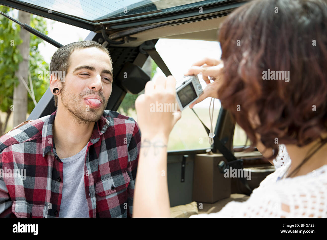 Woman taking picture of man sticking out tongue - Stock Image