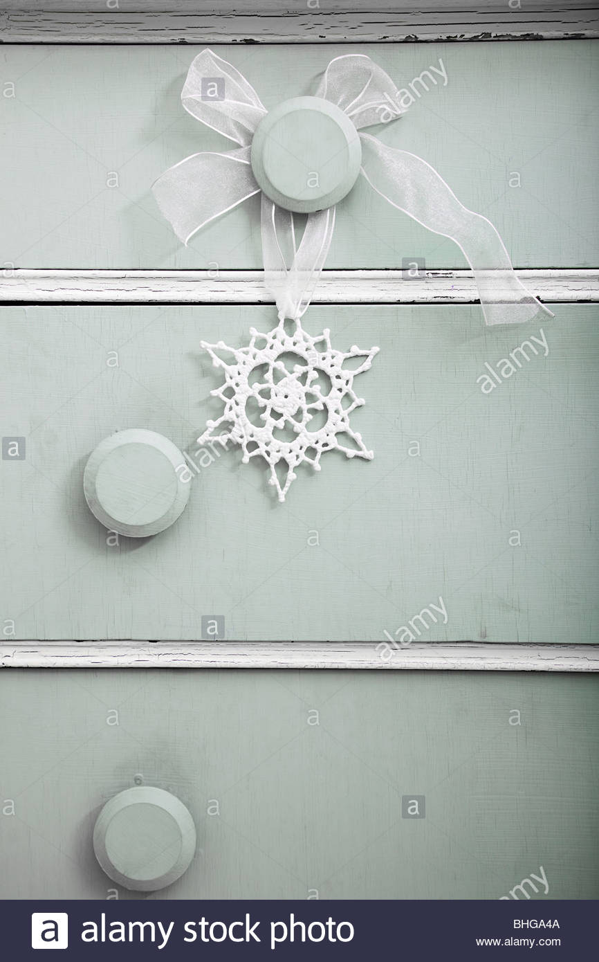 Snowflake decoration on dresser - Stock Image