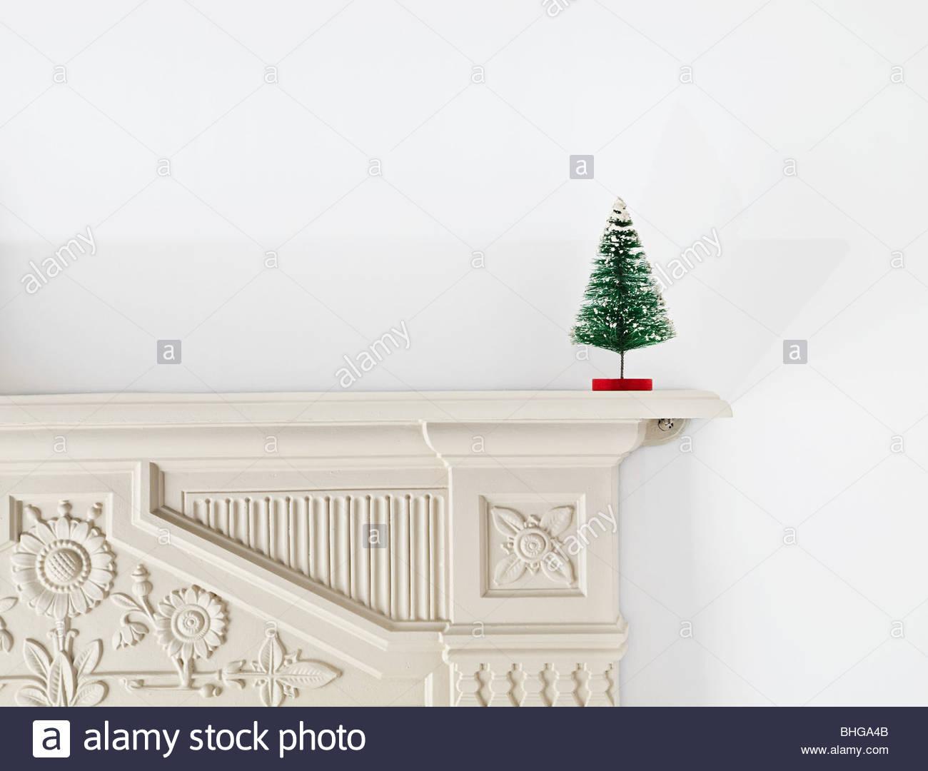 Miniature christmas tree on mantlepiece - Stock Image