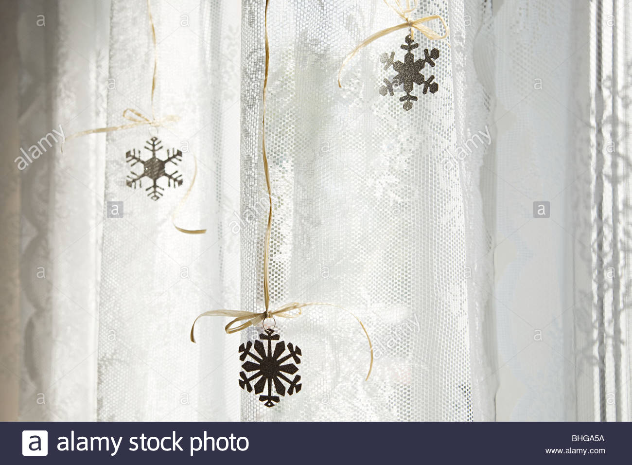 Snowflake decorations in window - Stock Image