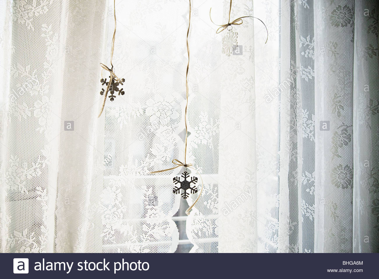 Snowflake decorations in window - Stock Image